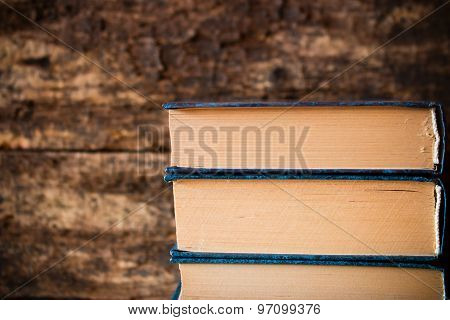 Three Old Books In A Stack Vertically On A Wooden Background