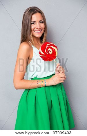Smiling young girl holding lollipop on gray background. Looking at camera