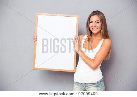 Happy casual woman holding blank board over gray background. Looking at camera