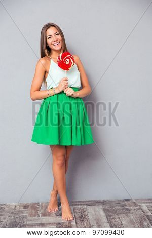 Full length portrait of a smiling young girl standing with lollipop on gray background