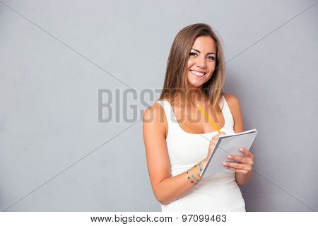Smiling young girl holding pencil with notebook over gray background. Looking at caera