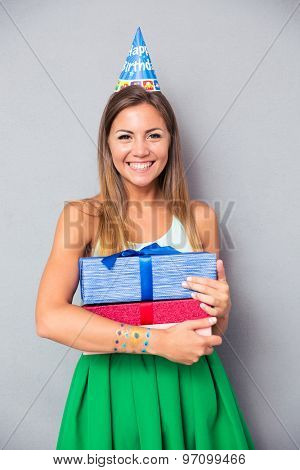 Smiling attractive girl in party hat holding gift boxes over gray background and looking at camera