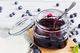 image of jar jelly  - homemade blueberry jam in a jar and fresh blueberries on a table - JPG