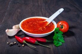 image of red hot chilli peppers  - red hot sweet chilli sauce over old wooden background - JPG