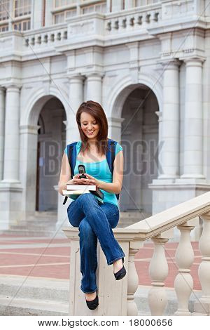 A young female student texting on campus
