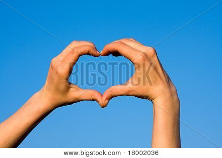 Hands forming heart against blue sky
