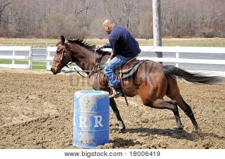 Man rounding a barrel during a barrel race