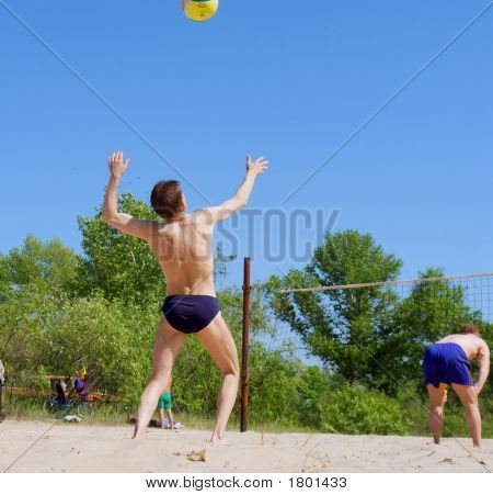 Two Men Play Beach Volleyball - Serve