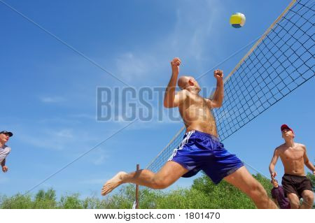 Four Men Playing Beach Volleyball - Balding Man Runs After Ball