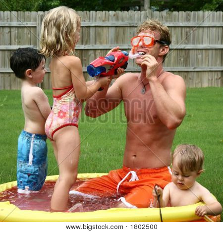 Boys And Girl Play With Dad In The Kids Pool