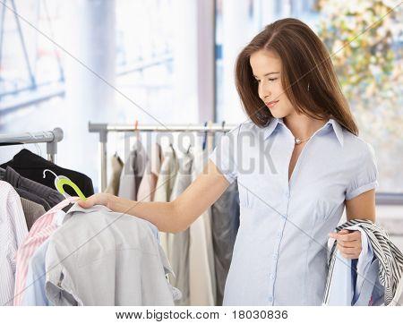 Jovem mulher olhando a camisa na loja de roupas, sorrindo.?