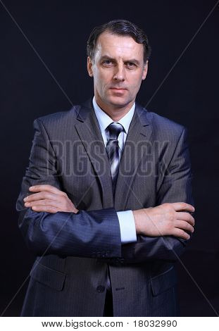 Portrait of a successful young business man with his hands folded on a dark background