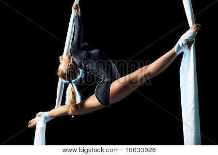 Young woman gymnast. On black background.