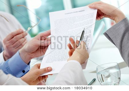 Image of human hands during discussion of paper