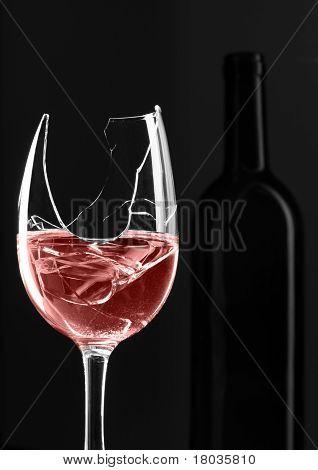 Vidro quebrado com garrafa no fundo