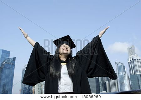 Happy graduate girl with city backdrop