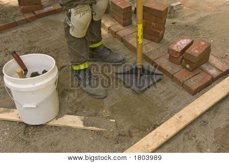 man tamping sand for brick patio work