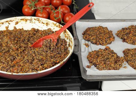 Cooked mixture of quinoa three varieties of beans vegetables in a pan and prepared patties to be baked. Mixing quinoa bean burger recipe at the kitchen stove top.