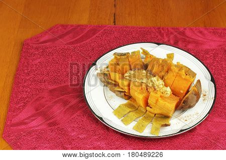 Boiled orange sweet potato cut open with butter and ground cinnamon on a round plate placed on a red place mat. Seasoned sweet potato served on a plate.