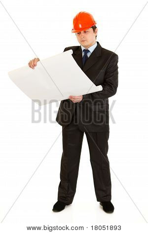 Concentrated businessman with helmet on head analyzing building projects isolated on white