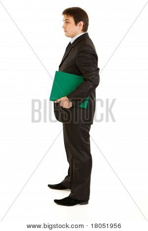 Full length portrait of serious modern businessman holding folder in hand isolated on white