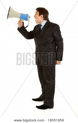 Full length portrait of frustrated young businessman yelling through megaphone isolated on white