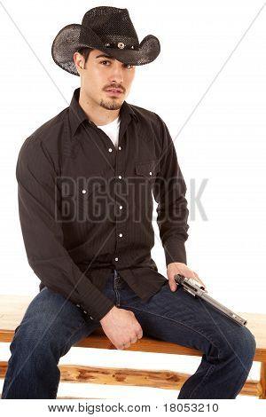 Cowboy Sitting With Gun On Leg
