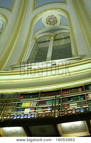 Walls of books and beautiful window of a library at night