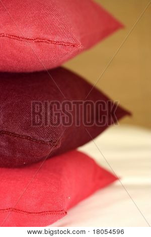 A stack of pink and maroon cushion on white made bed