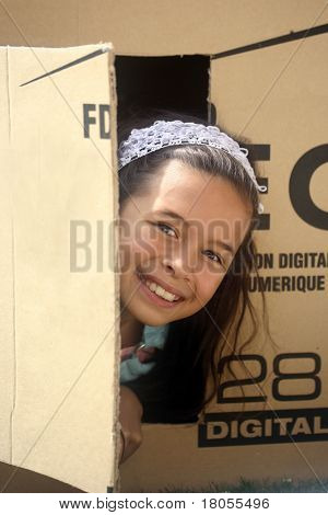 A girl plays hide and seek in a box