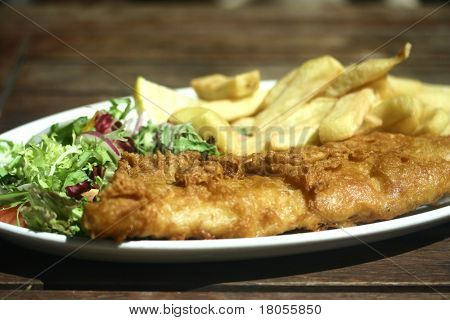 A plate of fish and chips with green salad on the side , on a wooden table