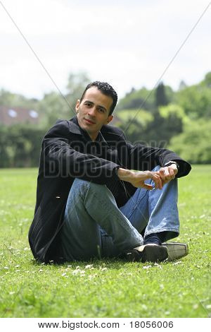 A young man poised and relaxed in an open grass field