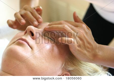 A masseur treating her client with holistic facial  massage