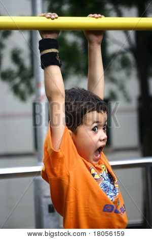 Concept : Hanging on . A young boy hangs on suspended in mid air, on playground bar