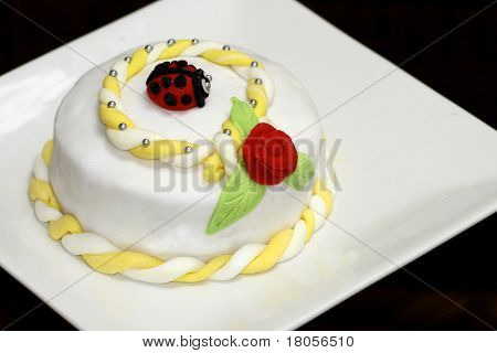 Close up image of a home-made birthday cake with a red rose, leaves and a ladybird made out of colored icing in various colors.