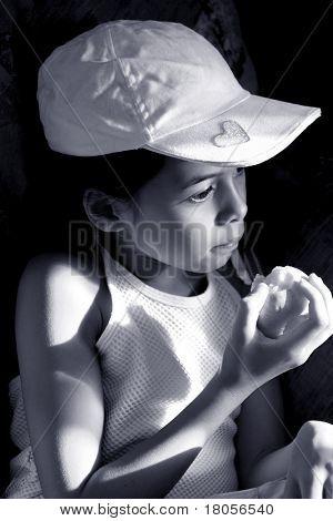 Una niña hace una pausa mientras se distrae mientras comía una manzana. Prestados clásico blanco y negro
