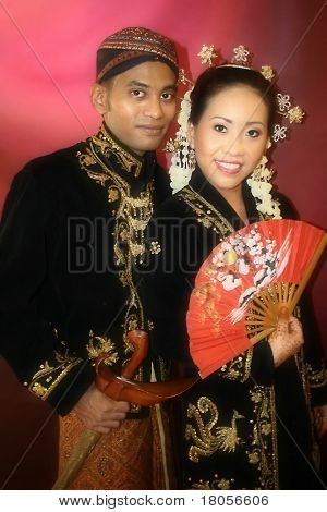 A Malay bride and groom in their traditional Javanese costume on the day of their wedding