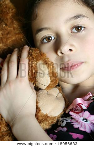 A young girl with pretty brown eyes enjoying a cuddle with her favourite cuddly bear.