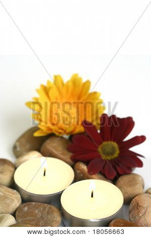 Therapy stones and fresh chrysanthemums with lighted candles suitable for spa setting and relaxation therapy, isolated on white with copyspace
