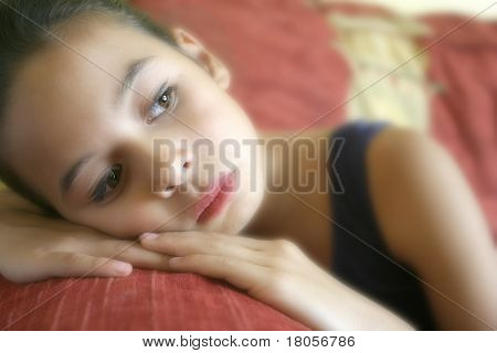 A young girl lost in thought as she daydreams.