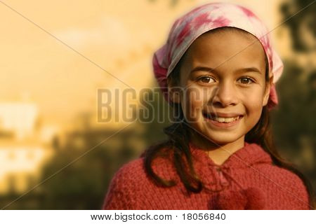 A young girl with pink bandanna showered by the glow of the evening sun