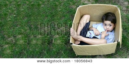 A young boy plays hide and seek in a cardboard box, with copyspace
