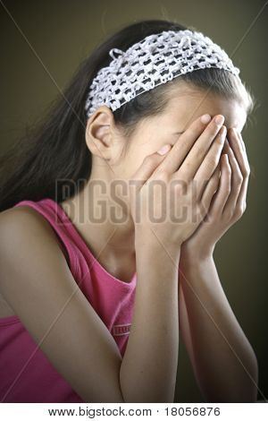 A young girl has both hands covering her face showing despair and sadness.