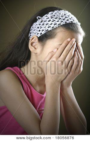 Ein junges Mädchen hat beide Hände über ihr Gesicht zeigen, Verzweiflung und Traurigkeit.