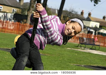 A young girl laughing happily as she rides on the playground pole on a warm day.