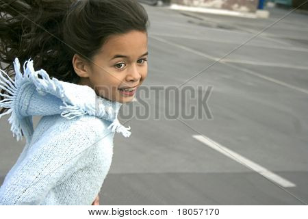 A young girl with brown hair having fun playing chase showing movement blur.