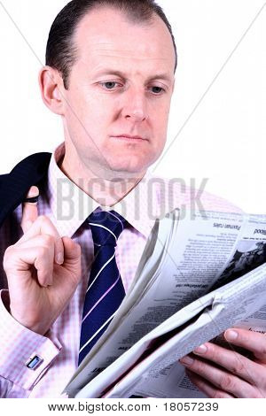 A businessman catching up on his newspaper, with his coat slung on his shoulder suggesting a slight casualness, isolated against white.