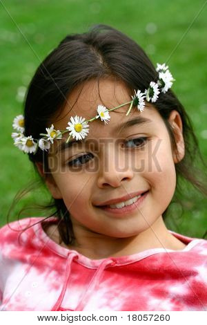 A girl of mix parentage showing off her daisy chain, enjoying the sunshine.