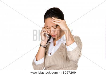 A businesswoman feeling despair as she listens to the news over the mobile phone, isolated on white.