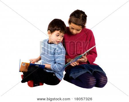 A little girl sharing her story book with her brother, isolated on white.